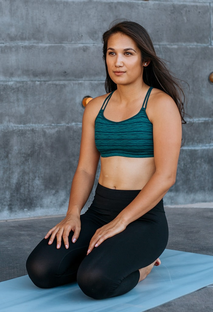 Woman sitting on a yoga mat in workout clothes