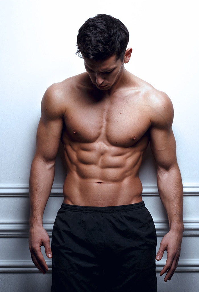 Man with his shirt off, showing his abs