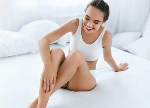 Woman touching her legs after unwanted hair reduction treatments
