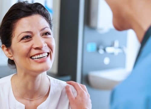 Happy woman talking to her doctor after lesion removal