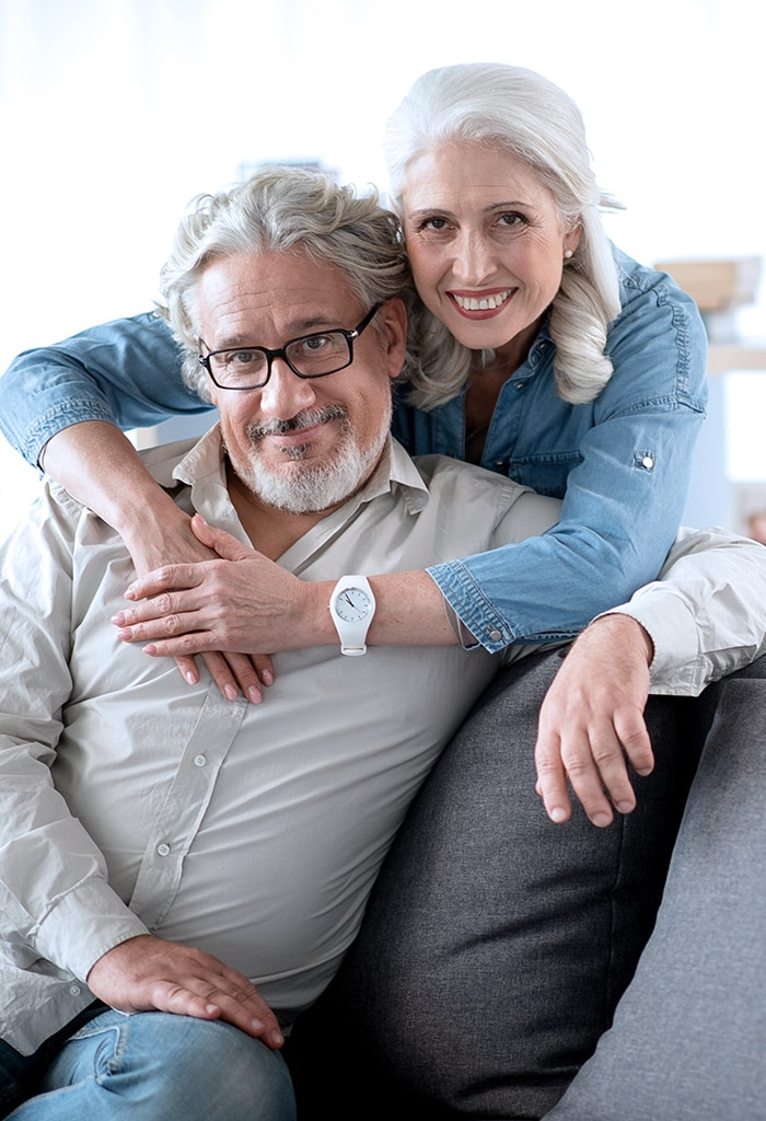 Older couple holding each other in their living room