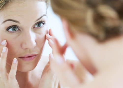 Woman looking at her skin in the mirror after wrinkle reduction